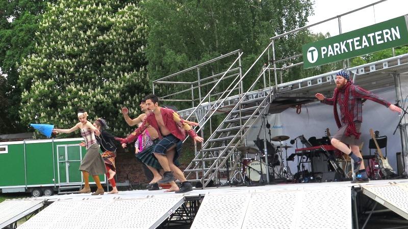 Fem dansare i rörelse på en vit scen i grönskande parkmiljö.