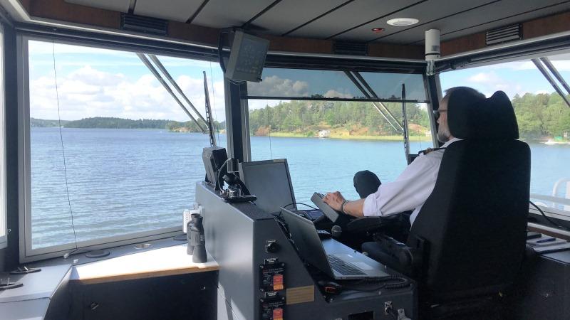 I styrhytten med stora fönster ser man kapten i vit skjorta snett bakifrån i stor fotölj. Utsikt över vatten, till höger land i sommargrönska.,