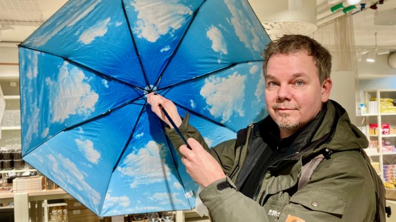 Man håller i ett uppslaget paraply som har ett tryck på insidan av ljusblå himmel med vita moln.