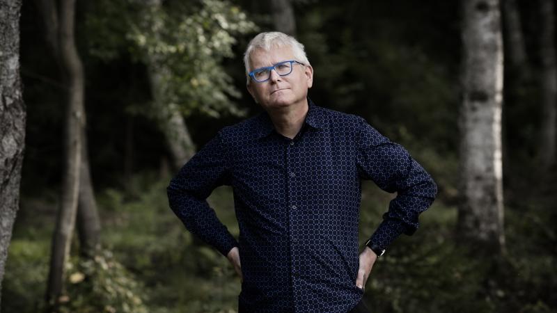 Per Wirtén har kort grått hår och glasögon med ljusblå bågar.
