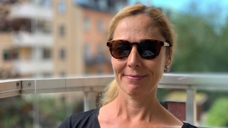 Leende kvinna med solglasögon och rödblont hår samlat i tofs i nacken sitter på en balkong med bostadshus och grönska i oskarp bakgrund.