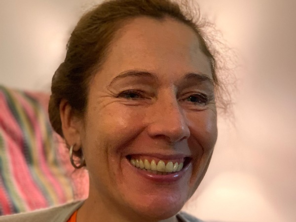 Ansikte på leende kvinna med ljus hy, och rödbrunt uppsatt hår.