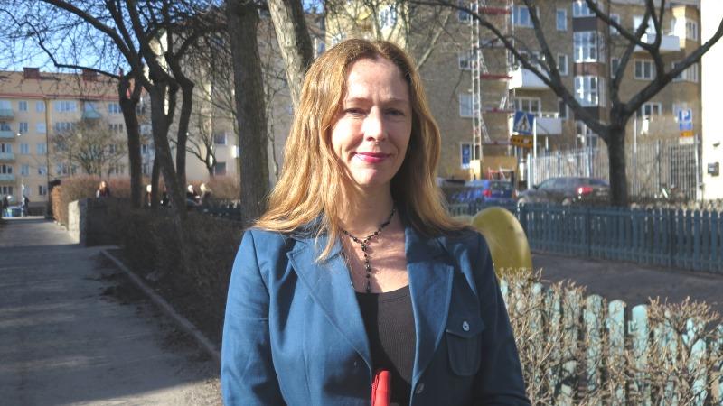 En kvinna med mellanbrunt hår och blå kavaj står utomhus.