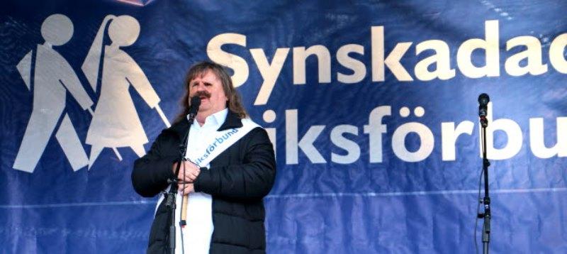 Gråhårig man står framför en stor SRF flagga i blått med vit text
