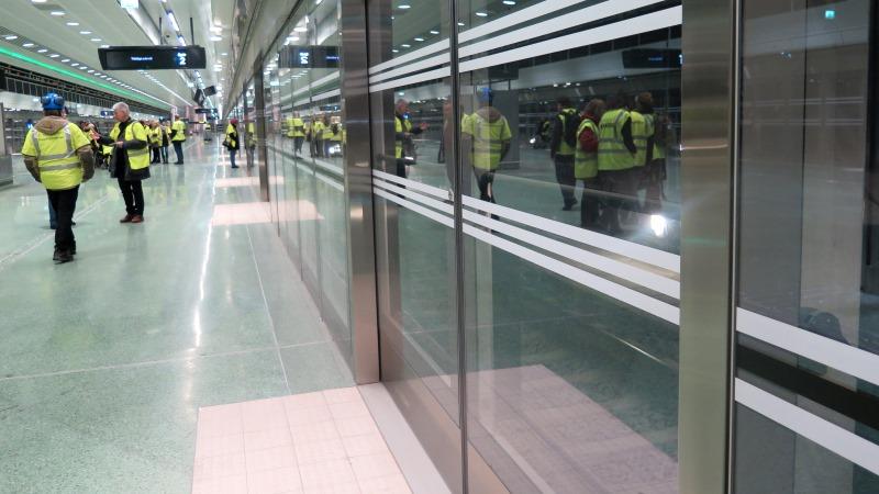 Bild på glasvägg invid en perrong och plattformsdörrar i glas.