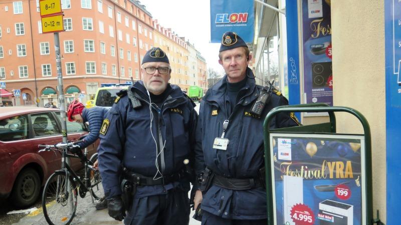 Två poliser bredvid godkänd skylt.