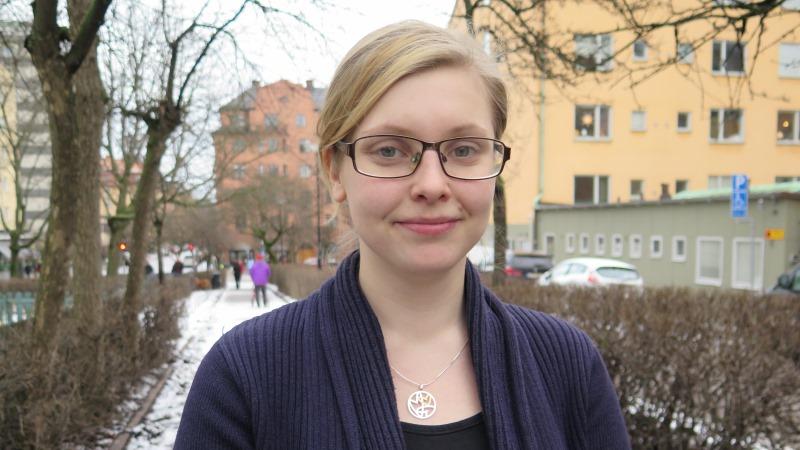 Ung kvinna med blont uppsatt hår och glasögon.