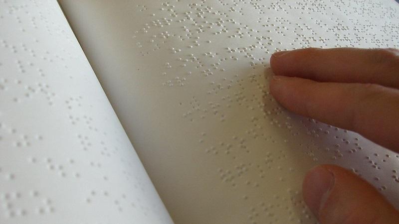 Ett uppslag med punktskrift. Till höger i bild syns en hand med fingrarna på skriften.