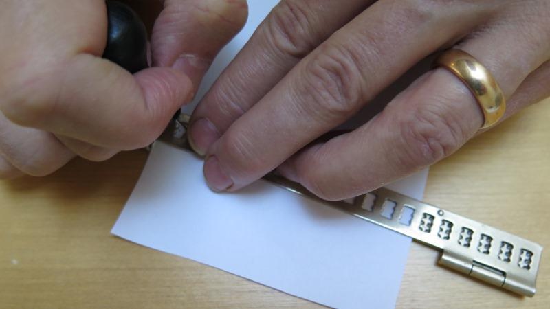 Närbild på två händer som skriver med reglett.