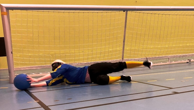 Blond liggande kvinna tar emot en blå boll framför ett Goalballmål