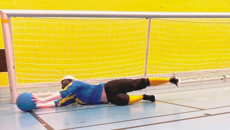 Blond kvinna slänger sig framför ett goalballmål, fångar blå boll