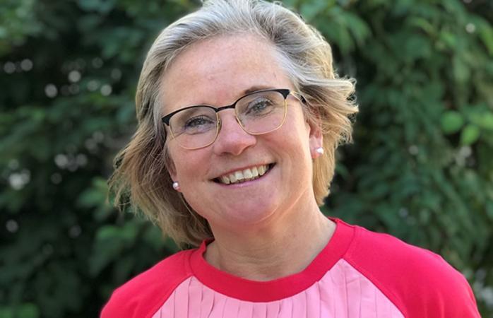 Ansikte på leende gråhårig kvinna med glasögon, framför grön buske.