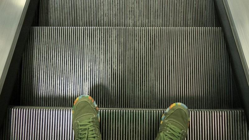 Tre steg i en rulltrappa sedda uppifrån. Ett par gröna skor sticker fram i bildens nederkant.