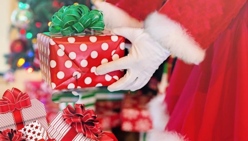 Julpaket lyfts upp ur säck av händer i vita handskar, röd tomtedräkt skymtar.