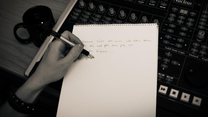 En hand som skriver i ett anteckningsblock. Bredvid står en kaffekopp.