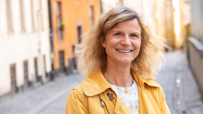Leende kvinna med axellångt vågigt ljus hår, gul jacka, står i stadsmiljö