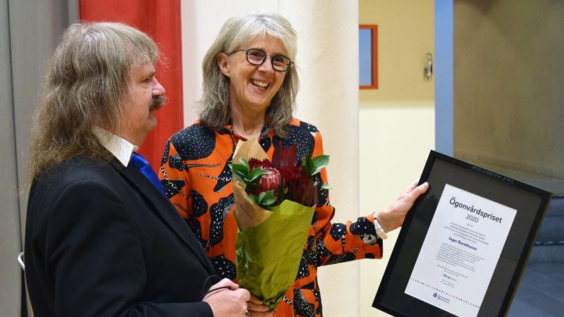 SRF:s Håkan Thomsson i profil intill en leende docent Inger Berndtsson som håller i ett diplom.