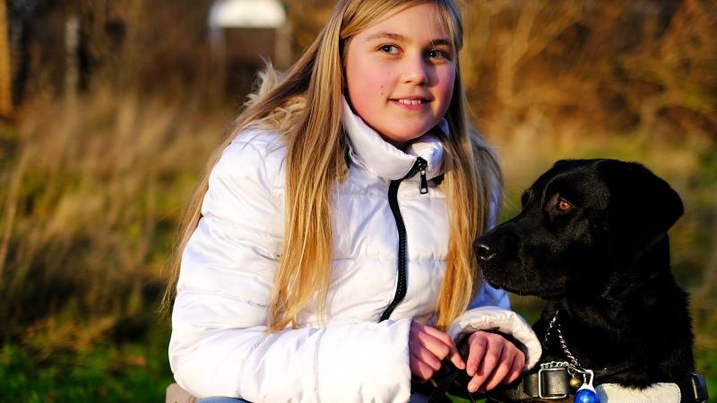 Ung flicka med ljust, långt hår, svart hund. Foto: Joachim Kåhlman