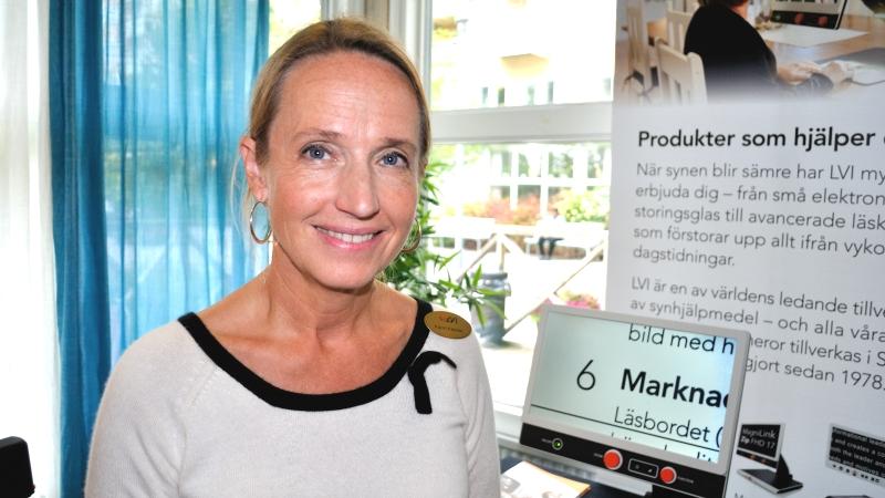 Karin Katzler från LVI. Bild på blond, medelålders kvinna i mässmiljö med förstoringshjälpmedel i bakgrunden.