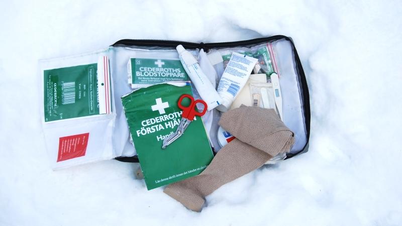 Första Hjälpen väska ligger uppslagen i snön, med diverse plåster och kompresser.