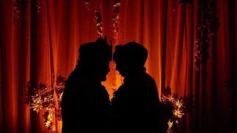 Silhuetterna av två personer som står med ansiktena lutade mot varandra och håller om varandra syns mot en bakgrund av en belyst röd ridå.