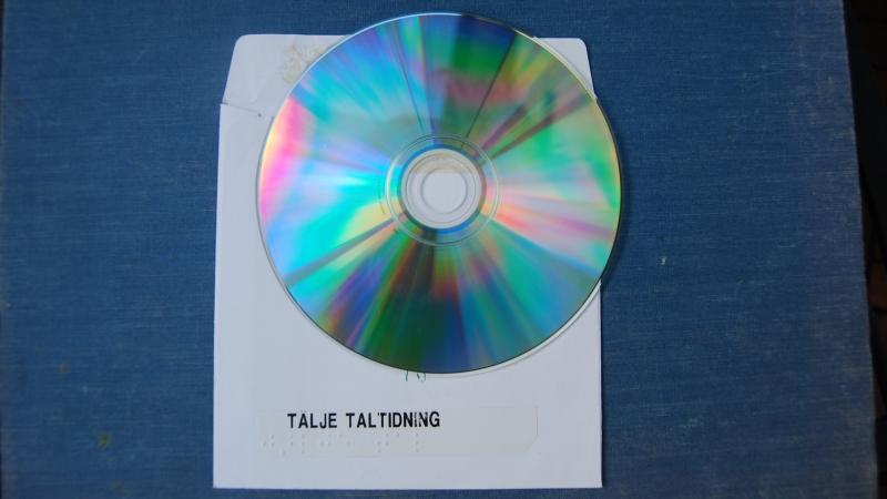 CD-skiva ligger på vitt cd omslag med text: Tälje taltidning. Blå bakgrund.