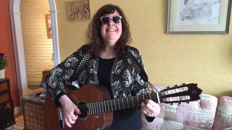Brunhårig leende kvinna med gitarr i knät, sitter i en ljus soffa