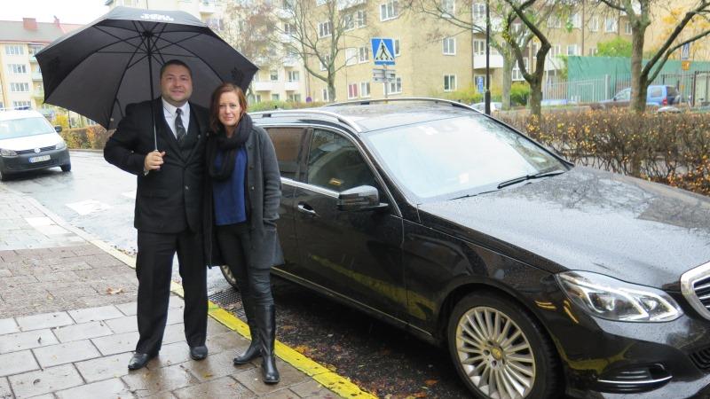 Mia Fahlén med chaufför poserar framför taxibilen.