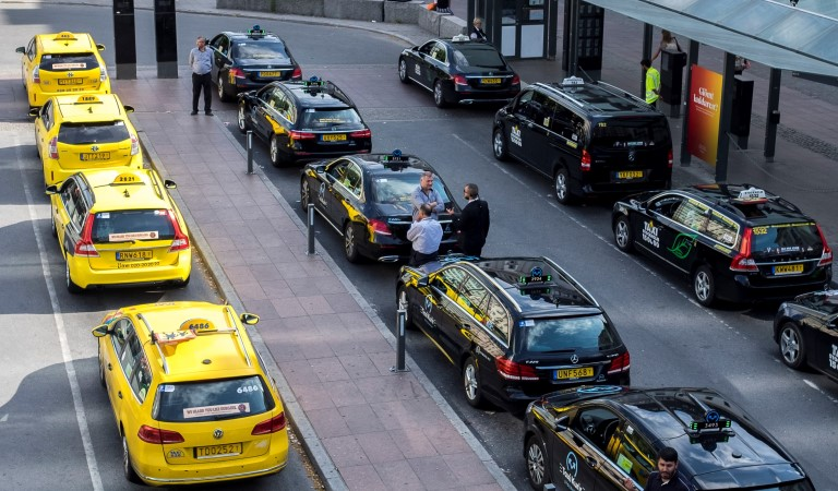 Tre rader parkerade taxibilar vid en hållplats. Gula bilar på rad i vänsterkant, resten är svarta. Några förare står utanför bilarna och väntar.