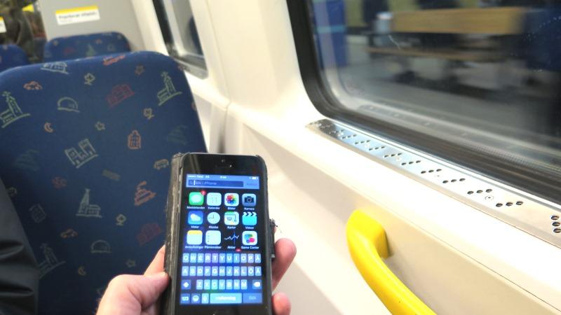 Bild på hand med mobil i tunnelbanevagn.
