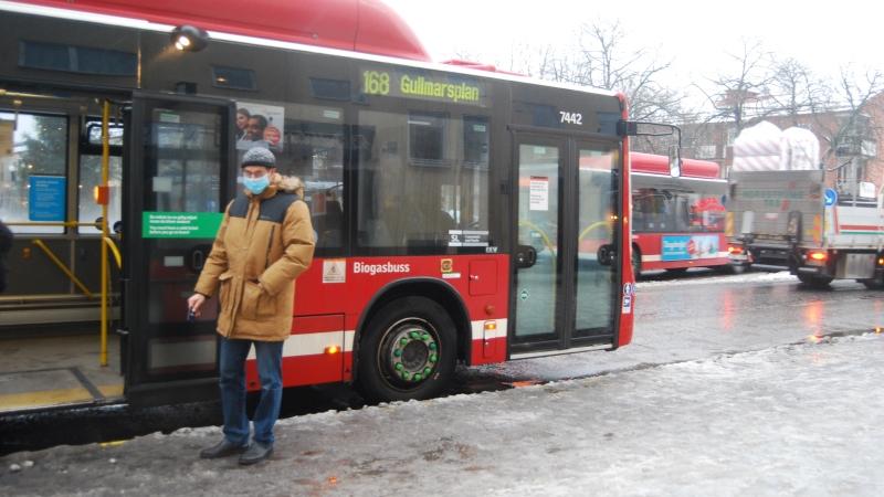 Man med blått munskydd står framför röd SL buss.