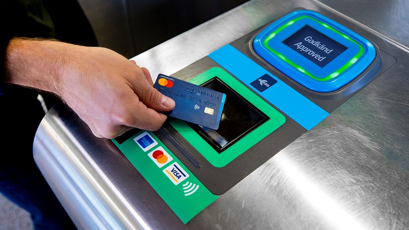 Hand som lägger betalkort på biljettläsare i tunnelbanespärr.