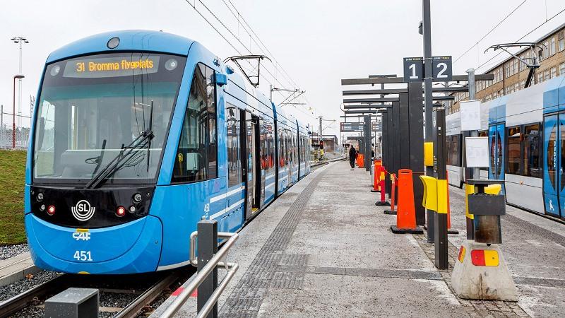 Blå spårvagn vid plattform.