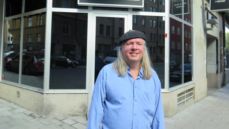 Ulf Nordquist i blå skjorta, långt grått hår och svart basker.