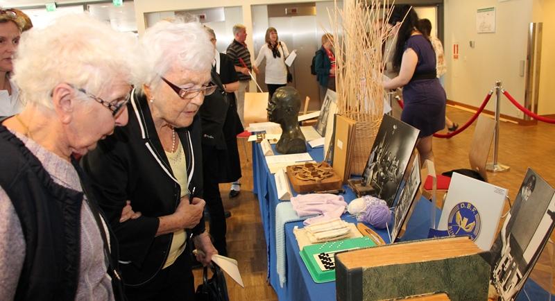 Två damer står och beskådar det som finns i montern för SRF:s museum. Damerna håller armkrok och har vitt, lockigt hår.