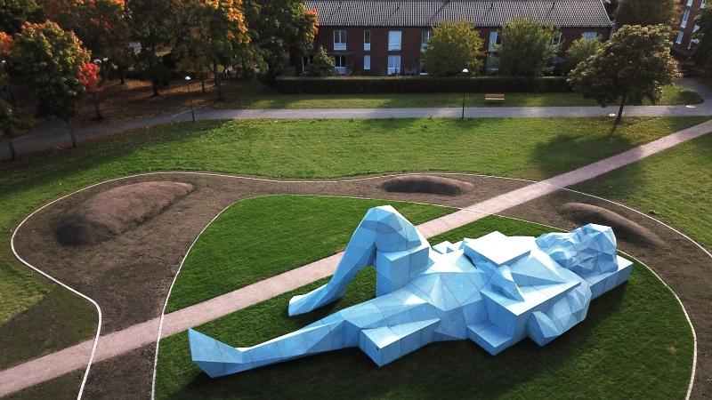 Enorm ljusblå betongskulptur av liggande man på gräsmatta i park