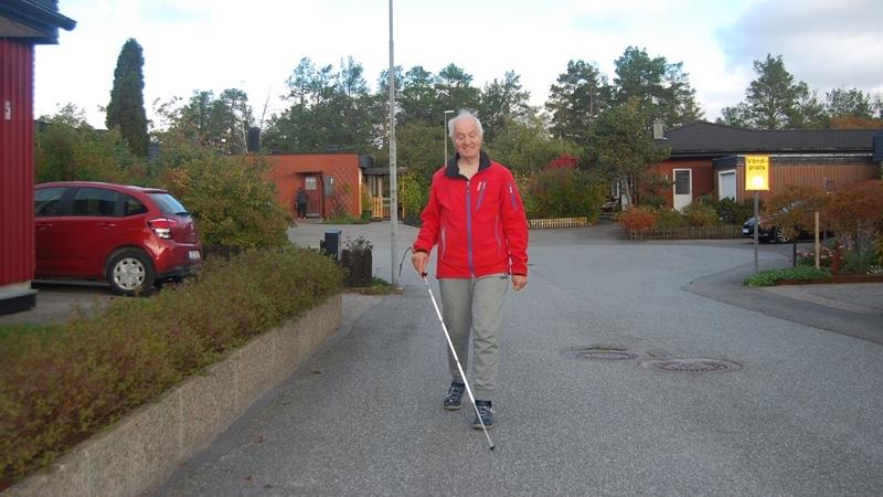 Äldre man i röd jacka och med vit käpp går på gata i villaområde