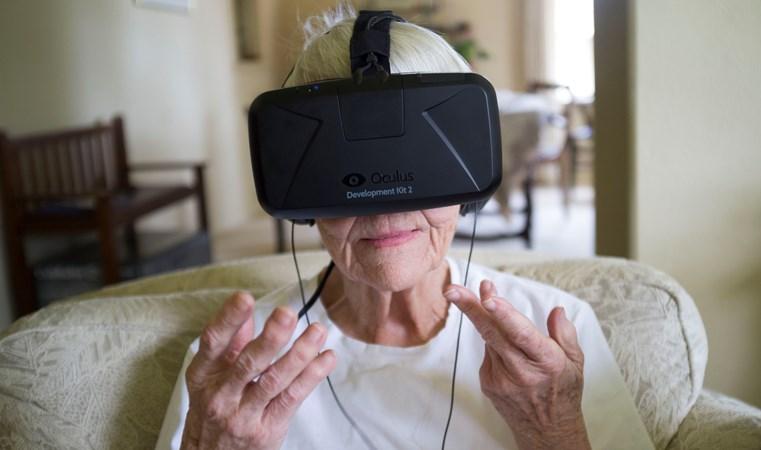 En äldre kvinnas ansikte täcks till stor del av svarta VR-glasögon med fästrem över huvudet