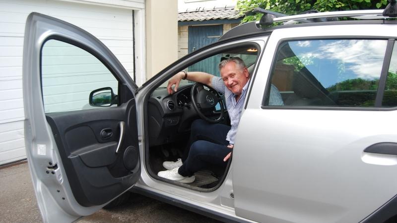 Äldre leende man sitter vid ratten med bildörren öppen.